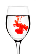 Clear wine glass with blood drops dissolving into clear liquid.