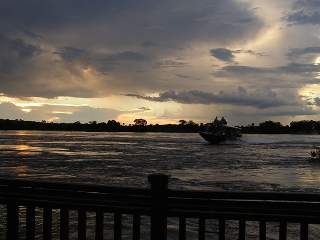 Boats on the river at dusk. The mighty Zambezi, just above Victoria Falls, southern Africa